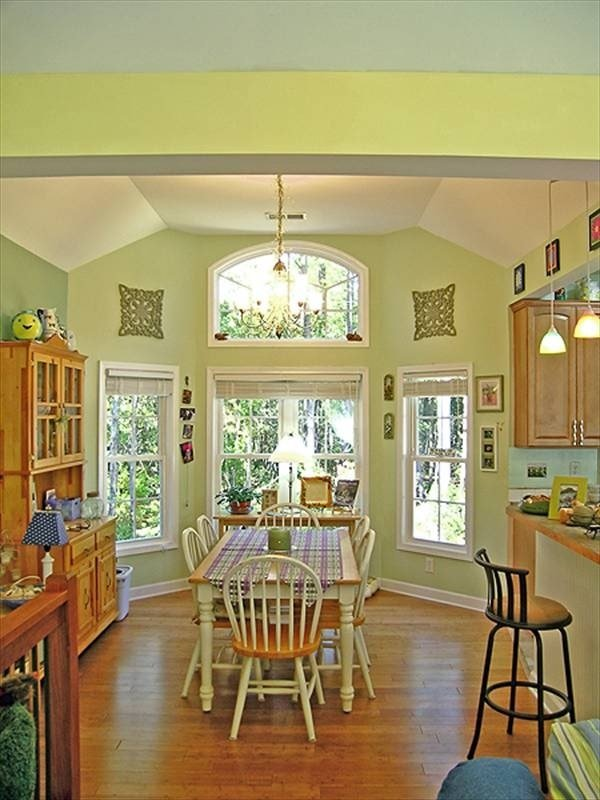 The dining area offers a wooden display cabinet, round back chairs, and a rectangular table topped with checkered runners.