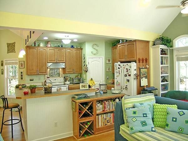 The kitchen has white appliances, wooden cabinetry, and a beadboard peninsula complemented with a round bar stool.