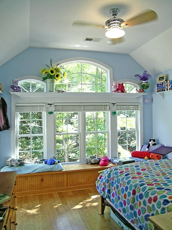 Primary bedroom with light blue walls, coved ceiling, and a window seat.