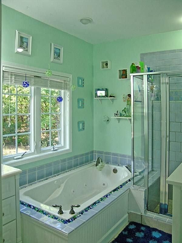 The primary bathroom has a walk-in shower and a drop-in bathtub fixed against the light green walls.