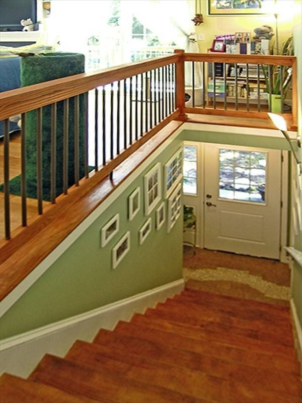 Wooden staircase adorned with white framed wall arts. It leads down the foyer with french entry door.