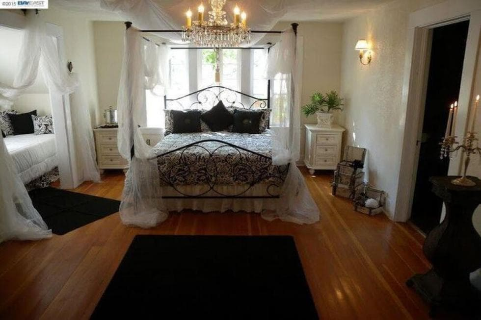 This bedroom has a wrought-iron four-poster bed with curtains that go well with the light tone of the walls complemented by the hardwood flooring. Image courtesy of Toptenrealestatedeals.com.