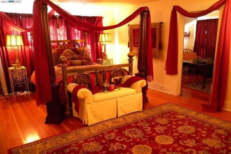 This other bedroom has a red theme to its area rug, bed and wall accents that go well with the beige walls. Image courtesy of Toptenrealestatedeals.com.