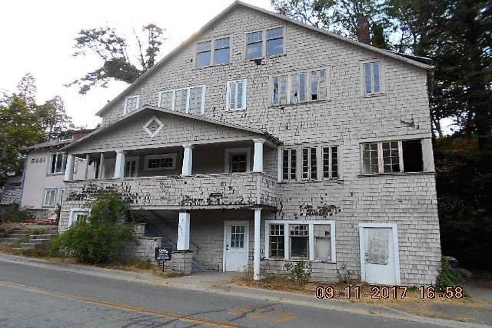 This is the rustic exterior of the 1911 house with a balcony and multiple windows on its facade. Image courtesy of Toptenrealestatedeals.com.