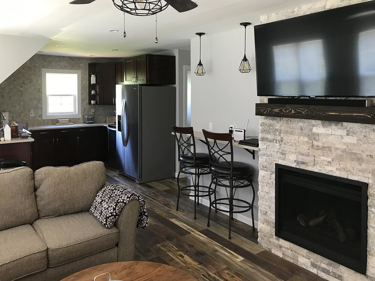 Shared kitchen and living room with a fireplace, gray sectional, built-in bar, dark wood cabinets, and slate appliances.