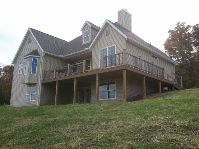 Rear exterior view showing the covered patio and expansive upper deck supported by wooden columns.