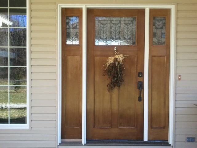 The home entry has a wooden front door adorned with stained glass panels.