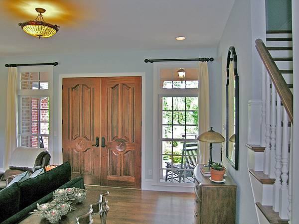 Foyer with a double entry door and a wooden console table paired with an arched mirror.