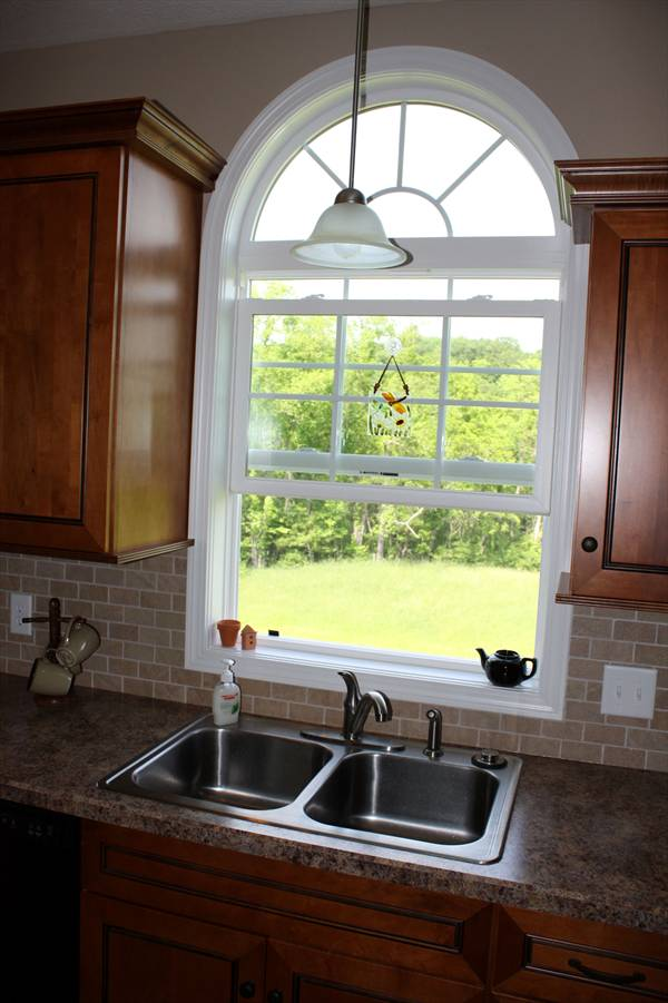 A double bowl sink fitted with chrome fixtures is placed under the large arched window.