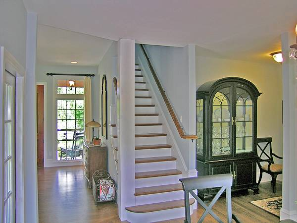 Traditional staircase leading to the bonus room. It is nestled in between the living room and dining area.