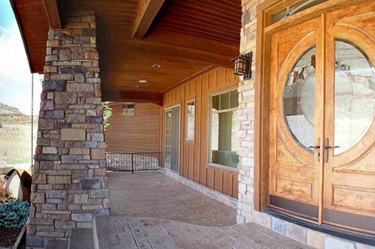 Front porch with stone brick columns and a wooden double entry door fitted with round glass panel.
