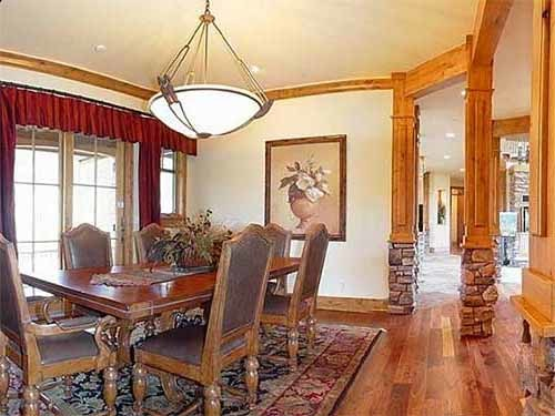 The dining room offers a glass dome pendant, cushioned chairs, and a wooden dining table sitting on a patterned area rug.