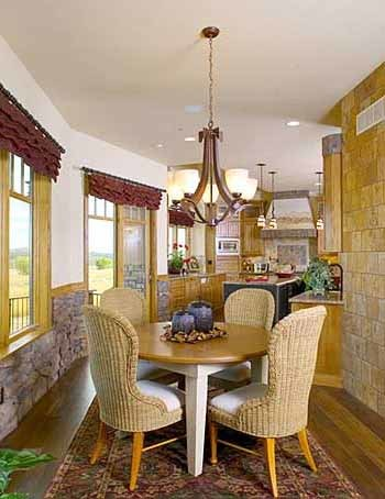 Breakfast nook with a floral area rug, wicker seats, round table, and glass chandelier.