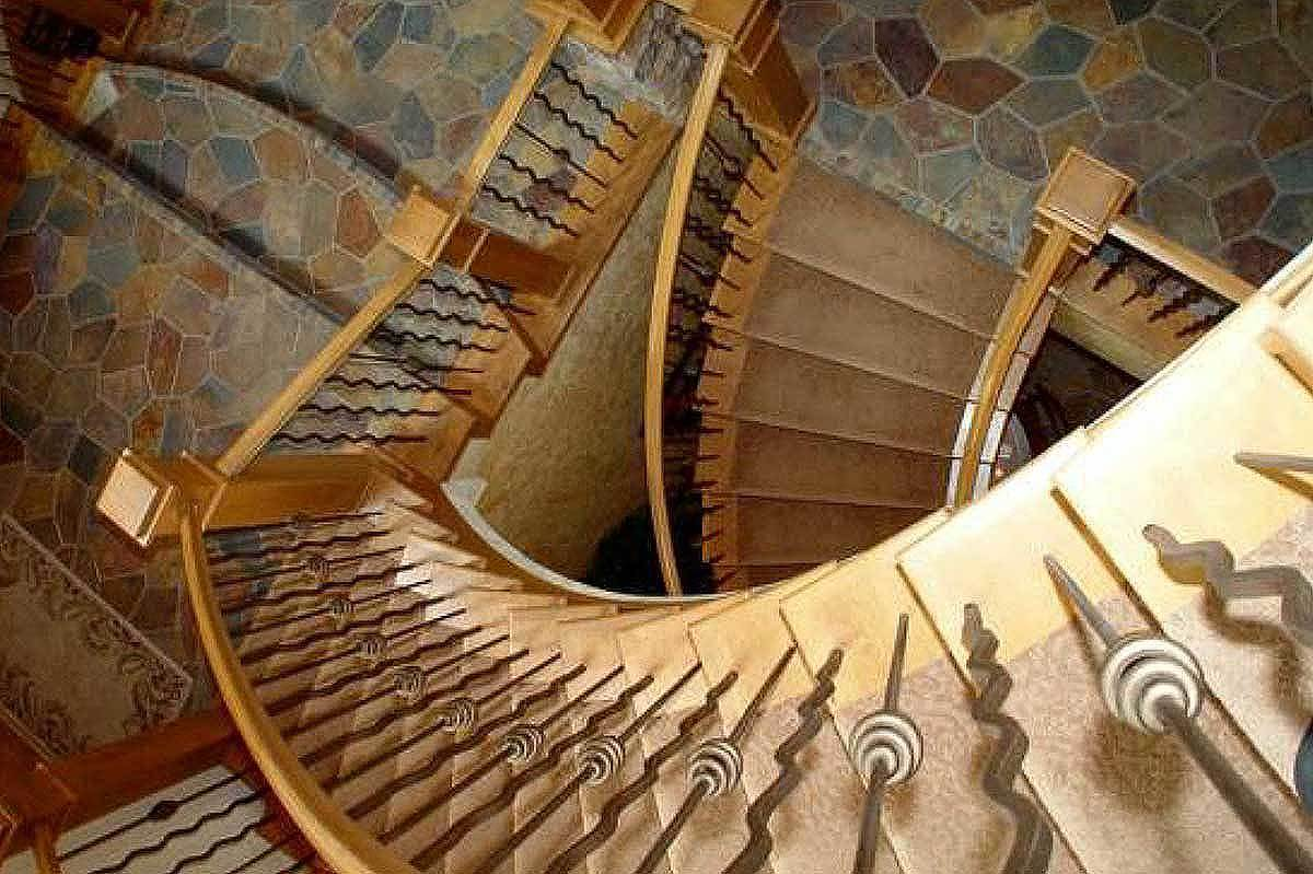 Top view of the winding staircase with wooden railings and posts along with wavy iron spindles.