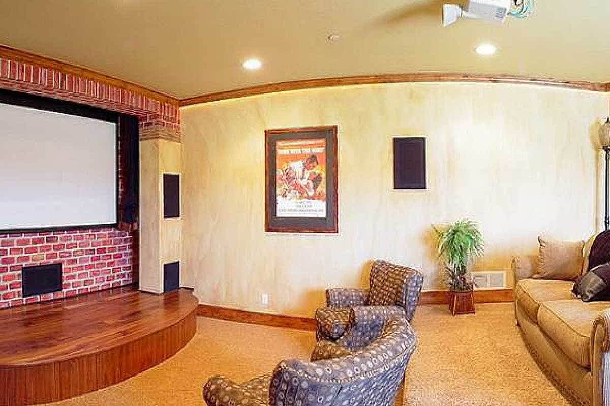 The home theater has cozy fabric seats, a wooden platform, and a red brick accent wall.