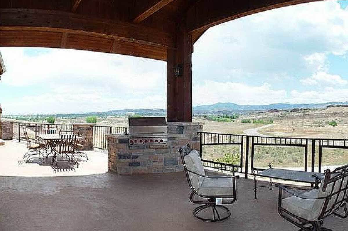 Covered deck with a summer kitchen and multiple seating areas overlooking the expansive landscape.