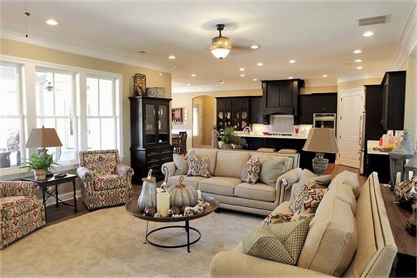 The living room has beige sectionals, patterned armchairs, and a round coffee table sitting on a velvet area rug.