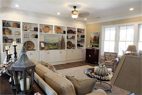 The cozy seats face the large white built-in cabinet filled with various decors.