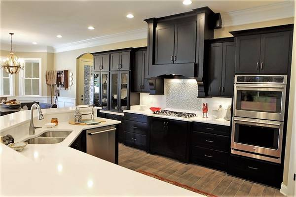 Kitchen equipped with stainless steel appliances, black cabinets, marble countertops, and a double bowl sink fitted on the two-tier island.