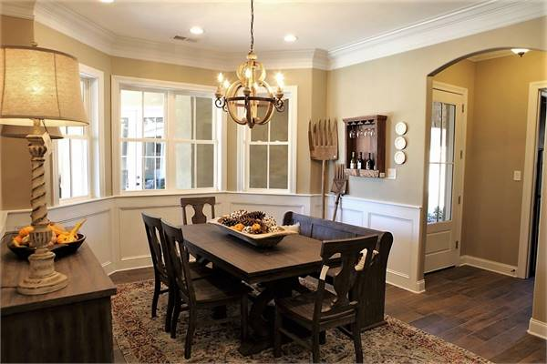 The dining area offers a spherical chandelier, wooden buffet, and a dark wood dining set.
