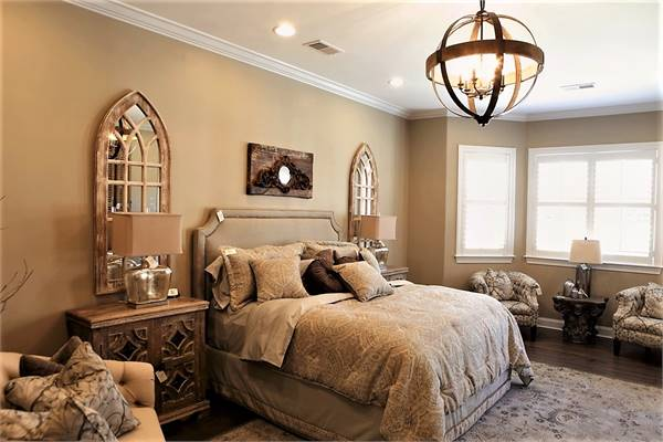 Primary bedroom with a bayed sitting area and a beige upholstered bed flanked by stylish nightstands and arched mirrors.