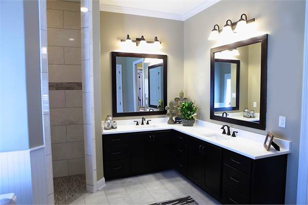 The primary bathroom features a dual sink vanity with black cabinets, marble countertops, and wrought iron fixtures.