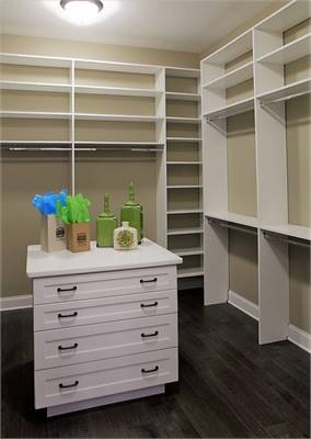 The primary closet showcases white shelvings and a marble top island.