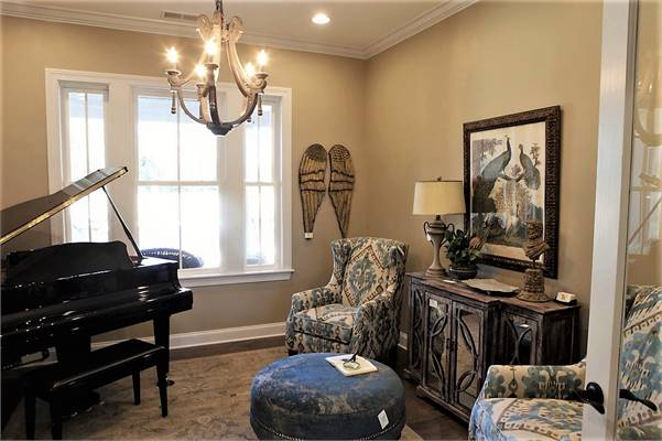 The study has classy wingback chairs, round ottoman, baby grand piano, and a rustic console table adorned by a framed artwork.