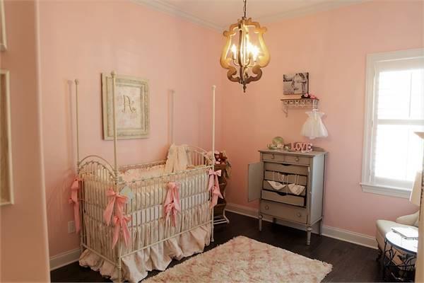 Nursery room with pink walls, dark hardwood flooring, skirted cradle, and a fluffy rug.