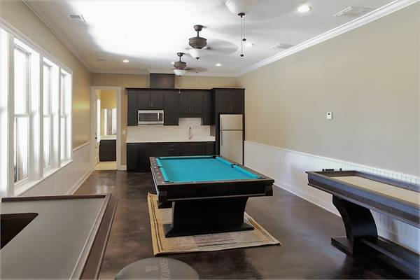 The pool house is complete with game tables, a kitchenette, and a full bath.