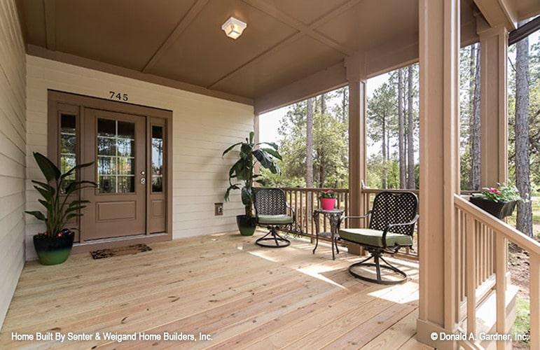 Front porch with a glazed entry door, perforated armchairs, small round table, and fresh potted plants.