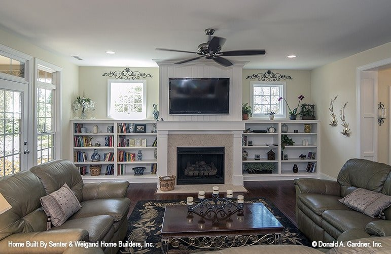 The living room has leather sofas, dark wood coffee table, and a fireplace flanked by white built-ins.