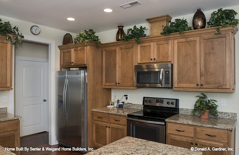 The kitchen is equipped with stainless steel appliances, granite countertops, and wooden cabinetry.