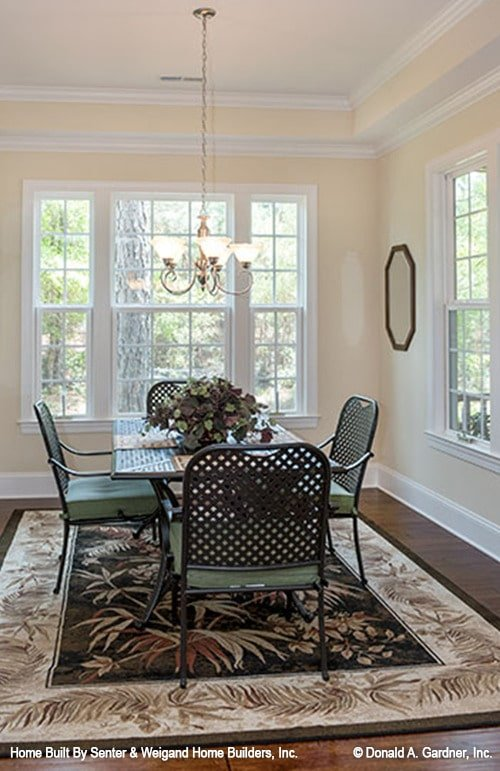 Dining room with a glass chandelier, cushioned armchairs, and a rectangular table sitting on a bordered area rug.