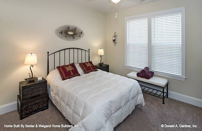 Another bedroom with cushioned bench, carved wood nightstands, and a metal bed placed under the oval artwork.