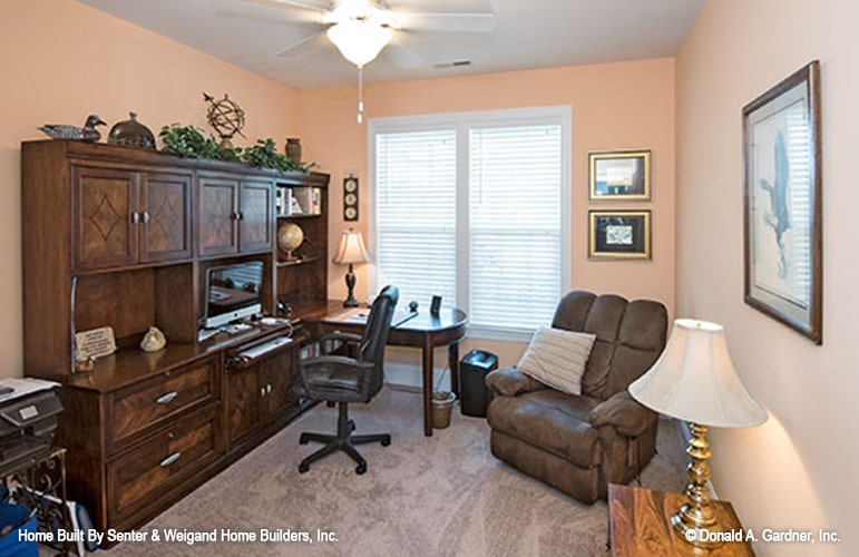 The study has salmon pink walls, wooden cabinet and desk, swivel chair, and cozy recliner.