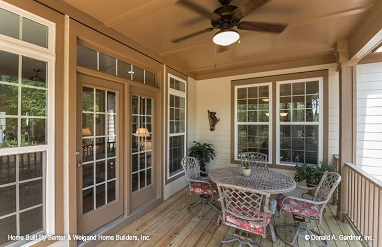 Rear porch with cushioned metal chairs and a round perforated table over wide plank flooring.