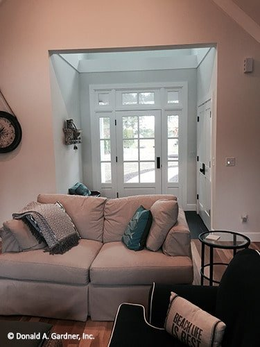 Foyer behind the gray couch showcasing a white framed entry door fitted with glass panels.