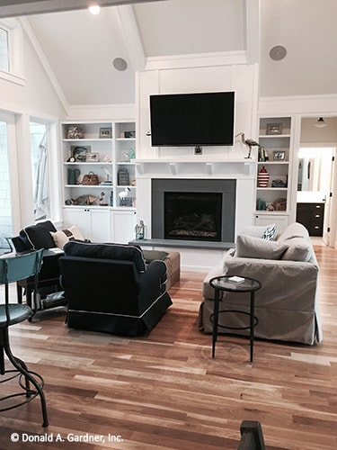 The living room has skirted seats, white built-ins, wall-mounted TV, and a fireplace.