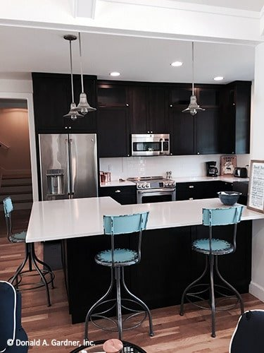Kitchen with black cabinets, stainless steel appliances, and an L-shaped peninsula complemented with blue counter chairs.