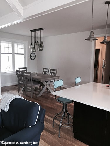 The dining room has a wooden dining table, matching chairs, and glass pendants.