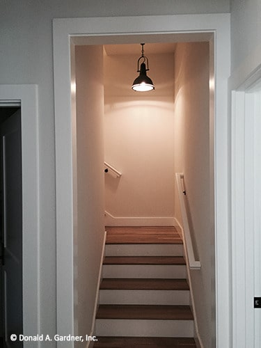 Staircase with white risers and wooden treads leading to the bonus room.