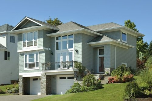 Front exterior view showing the upper balcony, double garage, and massive windows.
