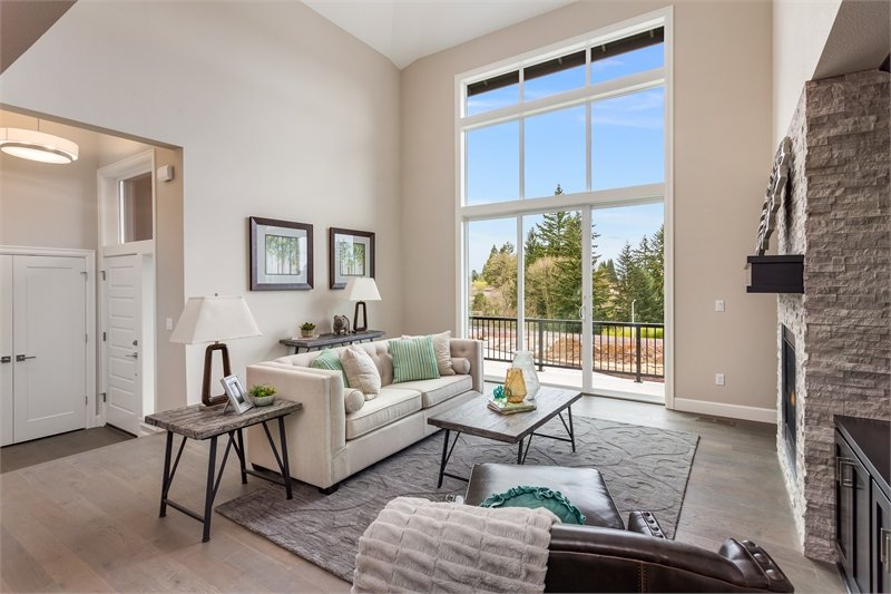 The living room has a beige sofa, leather lounge chair, wooden tables, and a stone fireplace.