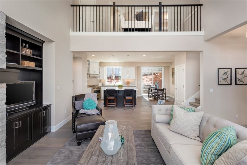 Sitting across the living room is the second-floor balcony and eat-in kitchen.