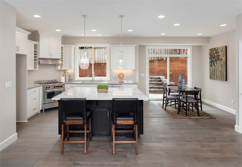 The eat-in kitchen has marble countertops, white cabinets, a breakfast island, and a rectangular dining set.