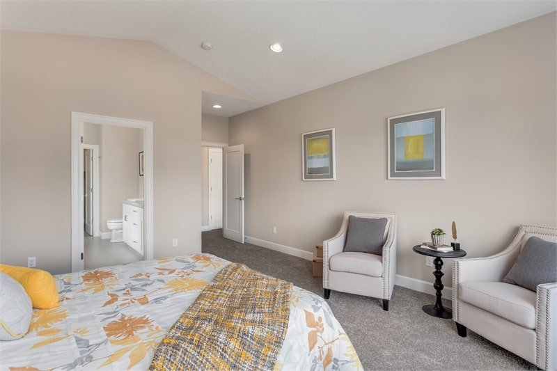 Primary bedroom with a cozy bed, cushioned armchairs, and framed artworks adorning the beige wall.