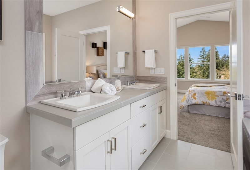 Primary bathroom with a dual sink vanity paired with a large wooden framed mirror.