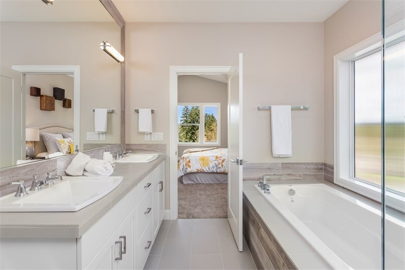 A farther view shows the drop-in bathtub fixed under the picture window.