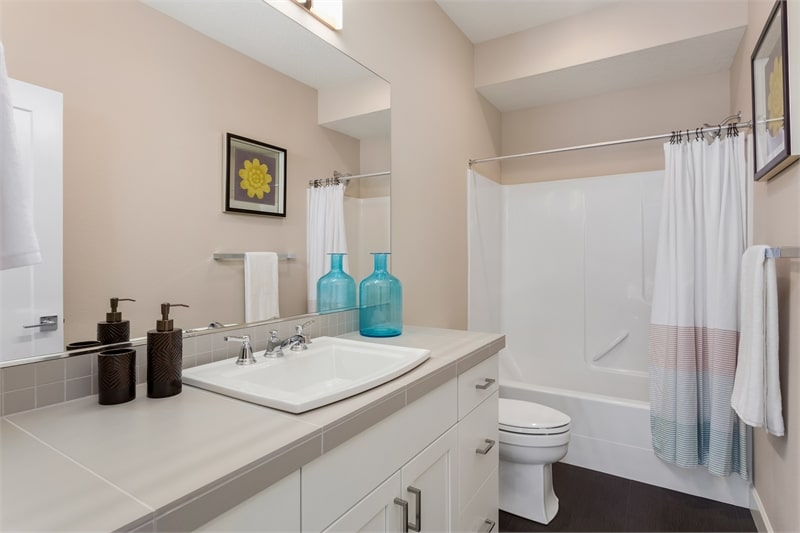 This bathroom offers a white vanity, a toilet, and a tub and shower combo.